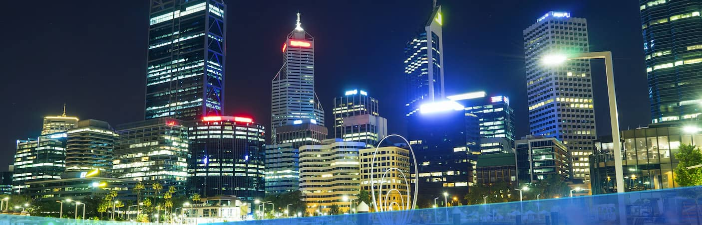 Driving into the commercial part of Perth city lit up with night lights.