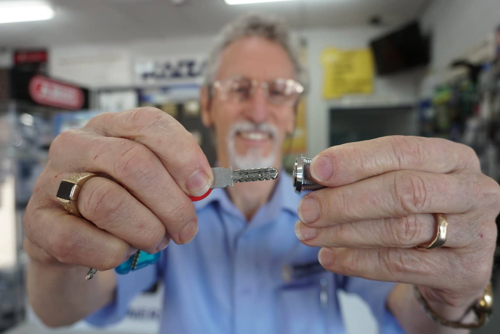 Man holding a key and lock cylinder in focus